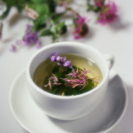 Beebalm and other flowers float in a cup of herbal tea made with catnip, motherwort, beebalm, lavender, and lemon balm.